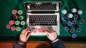 Laptop med spelmarker och spelkort runtomkring.